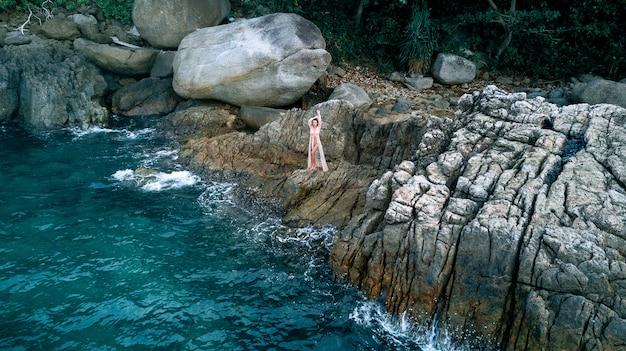 Vista aerea: foto sexy di una bella bruna in posa in piedi in un abito bianco mezzo nudo su una scogliera di una scogliera della riva del mare con le onde.