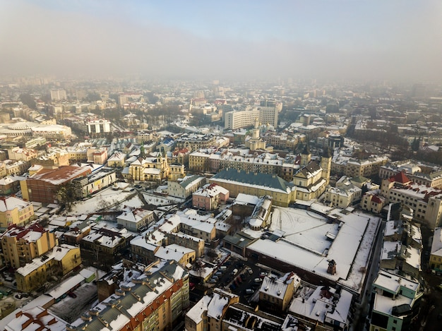 Vista aerea invernale bianco e nero del centro città moderna con edifici alti e auto parcheggiate su strade innevate.