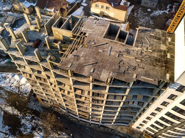 Vista aerea invernale superiore della città in via di sviluppo moderna con alto complesso di appartamenti in costruzione, auto parcheggiate, tetti e strade. infrastruttura urbana, vista dall'alto.