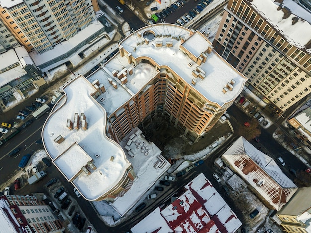 Vista aerea panoramica invernale in bianco e nero aerea della città moderna con tetto nevoso edifici alti edifici complessi, parcheggiate e auto in movimento lungo le strade. infrastruttura urbana, vista dall'alto.