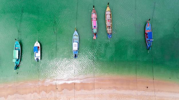 Vista aerea parte superiore giù dei pescherecci del longtail tradizionale tailandese nella bella spiaggia del mare tropicale