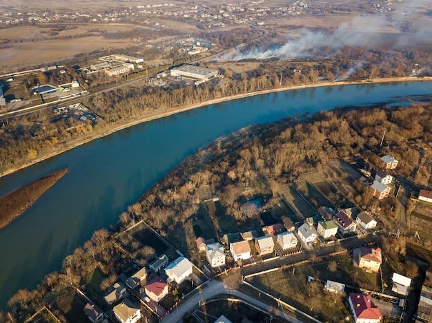 Vista aerea superiore del fiume che scorre attraverso la città. paesaggio rurale di case residenziali, strade e alberi in primavera o in autunno giorno. fotografia di droni.