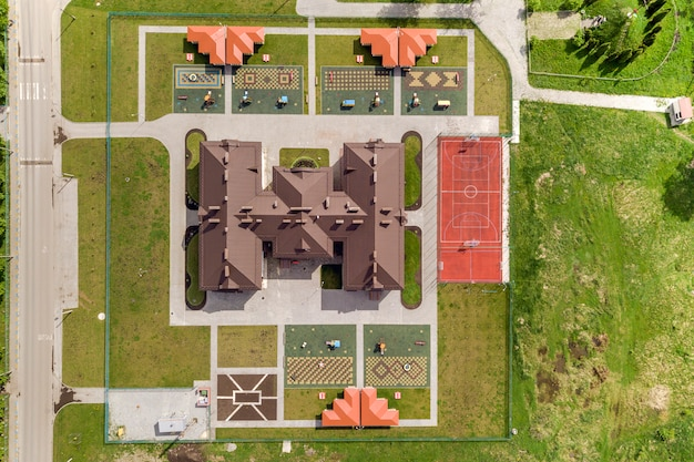 Vista aerea superiore del nuovo edificio prescolare e cortile con nicchie e prati verdi.