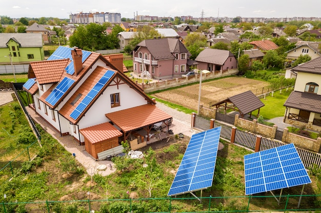 Vista aerea superiore del nuovo moderno cottage casa residenziale con sistema fotovoltaico solare lucido blu pannelli fotovoltaici sul tetto. concetto di produzione di energia verde ecologica rinnovabile.