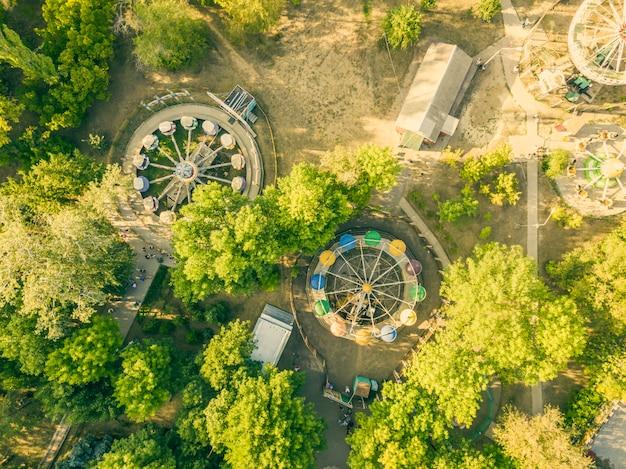 Vista aerea superiore del parco cittadino caorusel con bambini felici in vacanza estiva.
