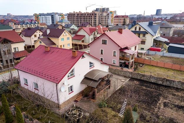 Vista aerea superiore della zona del sobborgo con belle case e automobili in giornata di sole.