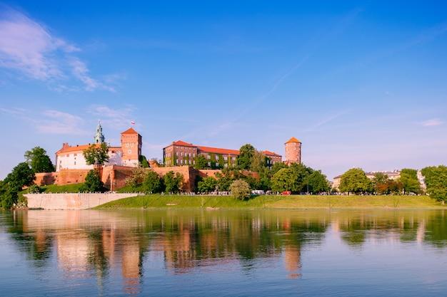 Vista al castello di wawel nella città di cracovia (cracovia), polonia, riflessa nel fiume vistola (wisla) in una soleggiata giornata estiva
