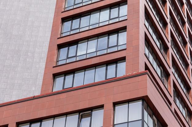 Vista al suolo della facciata moderna della costruzione con i mura di cemento rossi, finestre del balcone