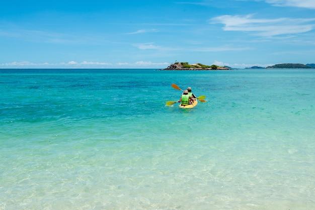 Vista all'indietro della famiglia che gioca kajak o canoa nel mare. famiglia persone viaggiatore kayak in mare. concetto di vacanza e outdoor. acqua dolce concetto di tempo della famiglia. natura chiara.