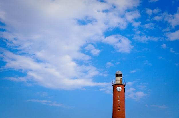 Vista alla casa leggera alta del mattone rosso sul fondo del cielo blu