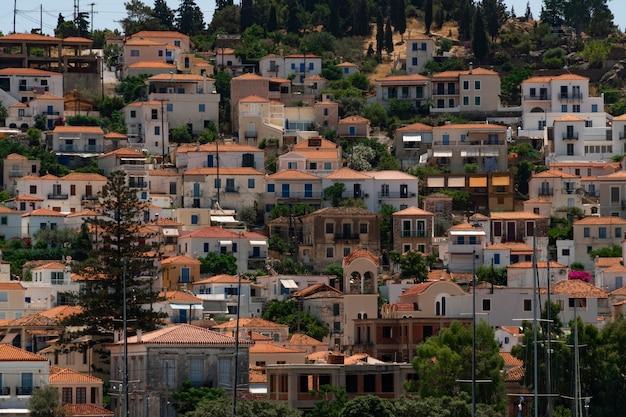Vista alle case bianche con i tetti rossi della città di poros, isole saronic, isola di poros, grecia.