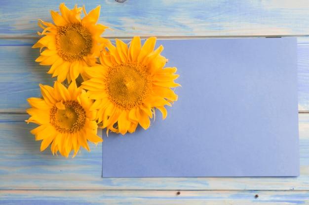 Vista ambientale dei girasoli gialli su carta in bianco sopra la tavola di legno