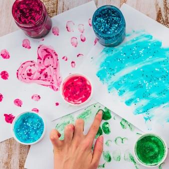 Vista ambientale della mano della persona che dipinge con il dito su carta bianca