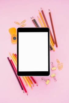 Vista ambientale della tabella digitale dello schermo bianco sui rifornimenti di scuola sopra la carta da parati rosa