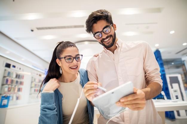 Vista bassa di giovani coppie sorridenti alla moda sveglie che collaudano il nuovo modello di una compressa con una matita nel deposito di tecnologia.