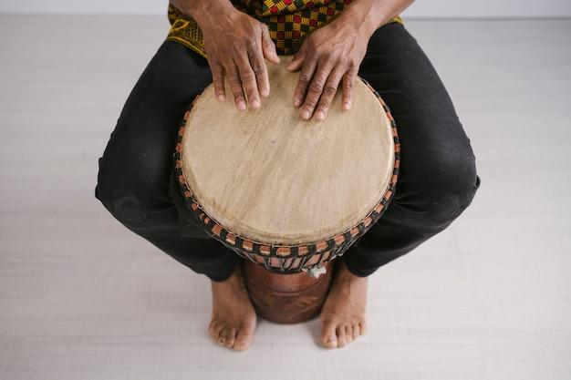 Vista da sopra del musicista maschio afroamericano che gioca i tamburi tradizionali a casa. concetto di classe di musica online. strumenti musicali per il tempo libero e l'apprendimento. ritmo nelle tradizioni etniche multiculturali.
