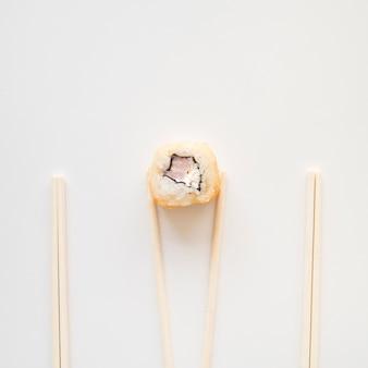 Vista da sopra le bacchette in possesso di un rotolo di sushi