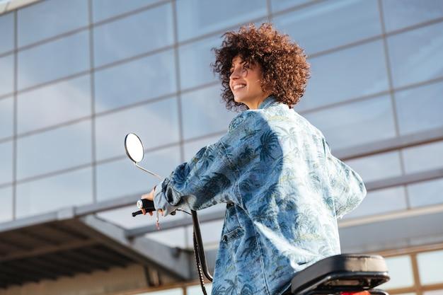 Vista da sotto della donna riccia sorridente che si siede sulla motocicletta moderna all'aperto e distogliere lo sguardo