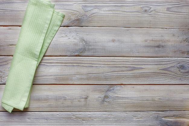 Vista da tavolo in legno grigio antico. tovagliolo verde chiaro.