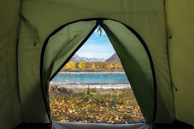 Vista da una tenda del fiume e alte montagne
