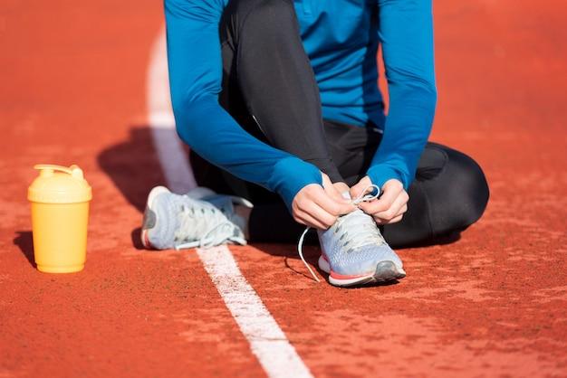 Vista da vicino, di un atleta che lega i suoi lacci. uomo stringendo i lacci delle scarpe seduto per terra su una pista da corsa.