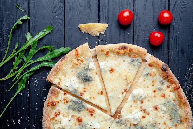 Vista da vicino sulla pizza con 4 formaggi: gorgonzola e parmigiano. feta, mozarella. messa a fuoco selettiva. fetta di pizza con ingridients. sfondo scuro cucina italiana. copia spazio