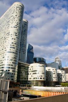 Vista dal basso dei grattacieli di vetro del quartiere degli affari di parigi la defense contro un cielo nuvoloso blu