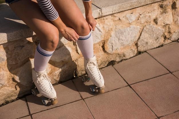 Vista dal basso della donna che indossa calze e pattini a rotelle