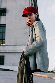 Vista dal basso della giovane donna alla moda con le mani in tasca