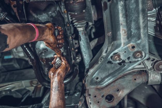 Vista dal basso delle mani di un meccanico che ripara un'auto
