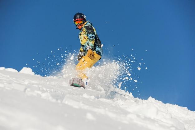 Vista dal basso dello snowboarder freeride che scivola giù per il pendio