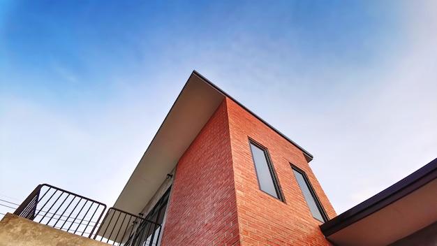 Vista dal basso di edificio con balcone decorato con mattoni contro cielo blu