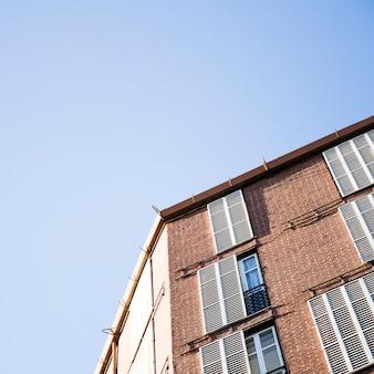 Vista dal basso di un edificio con finestre contro il cielo blu