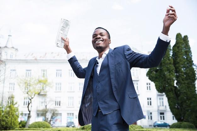 Vista dal basso di un giovane imprenditore spensierato tenendo il giornale alzando le mani
