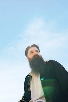 Vista dal basso di un giovane uomo barbuto in piedi sotto il cielo blu