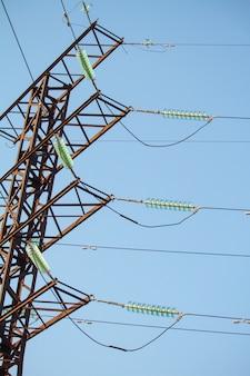Vista dal basso su linee elettriche ad alta tensione contro il cielo blu senza nuvole