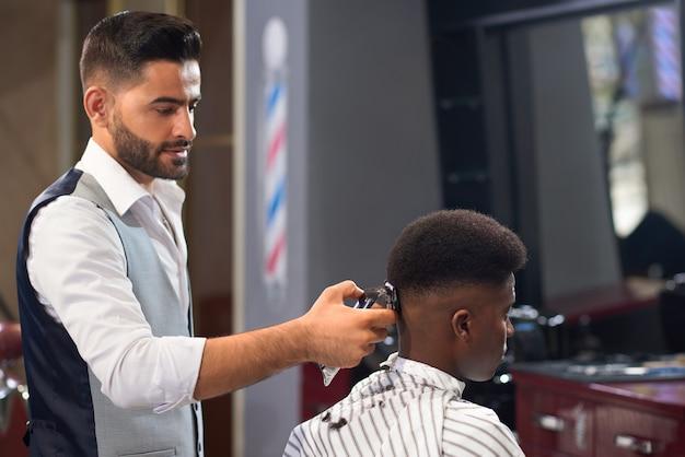 Vista dal lato del barbiere facendo un taglio di capelli alla moda nel negozio di barbiere
