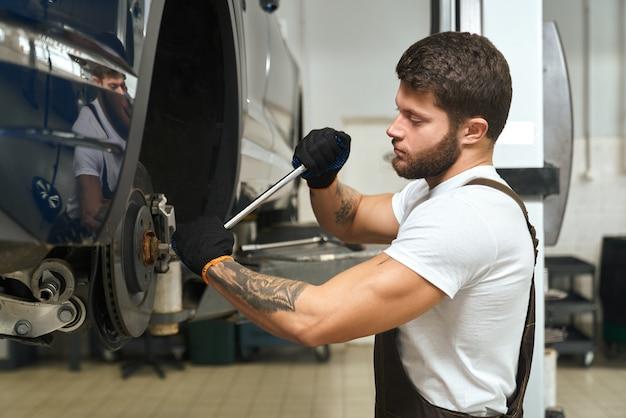 Vista dal lato di uomo bello cambiando la gomma della macchina