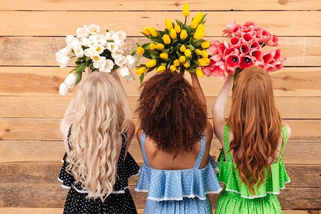 Vista dal retro di tre donne che tengono i fiori dei mazzi