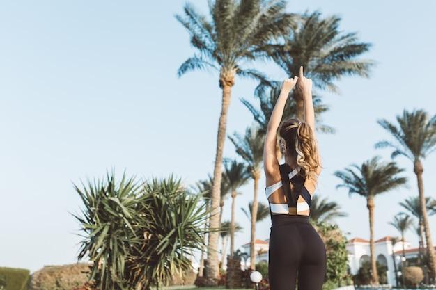 Vista dal retro gioiosa giovane donna in abiti sportivi che si estende su palme e cielo blu. mattina soleggiata, espressione di positività, vere emozioni, stile di vita sano.