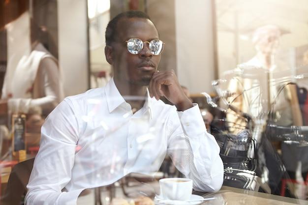 Vista dal vetro della finestra del bel ceo afroamericano pensieroso in camicia bianca e tonalità eleganti con caffè nero durante il pranzo, seduto da solo al caffè, con uno sguardo pensieroso, toccando il mento