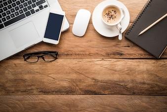 Vista dall'alto con spazio di copia, scrivania con computer portatile, cellulare, matita taccuino e caffè
