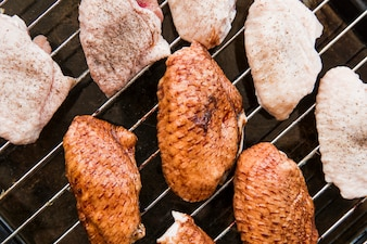 Vista dall'alto di ali di pollo crudo sulla griglia in metallo