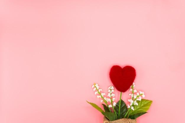 Vista dall'alto albero rosso a forma di cuore in un piccolo sacco legato con corda su sfondo rosa