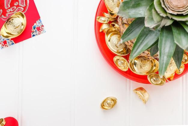 Vista dall'alto ananas con gruppo di lingotti d'oro nel vassoio rosso sul tavolo di legno bianco