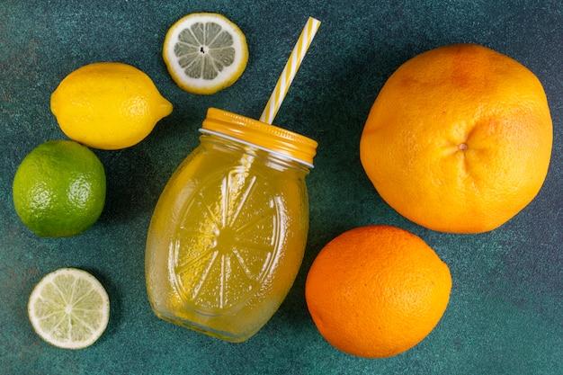 Vista dall'alto arancia con lime limone pompelmo e succo d'arancia su verde