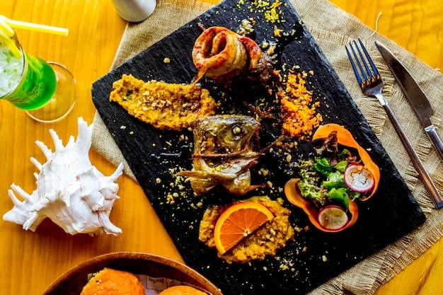 Vista dall'alto arrotolato pesce fritto con insalata di verdure e decorazione fetta d'arancia