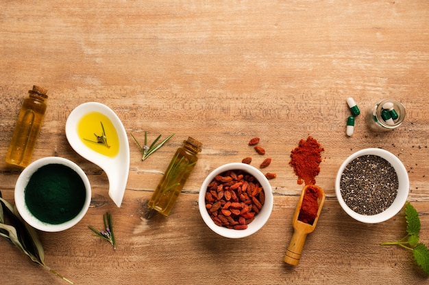 Vista dall'alto bacche di goji con olio e medicina sul tavolo