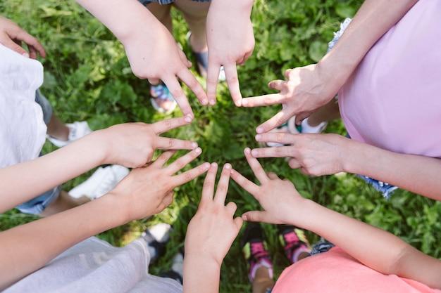 Vista dall'alto bambini che fanno una stella con le mani