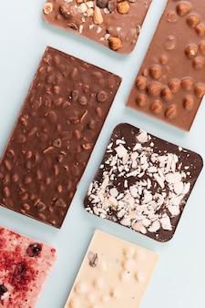 Vista dall'alto barrette di cioccolato con noci e frutti di bosco